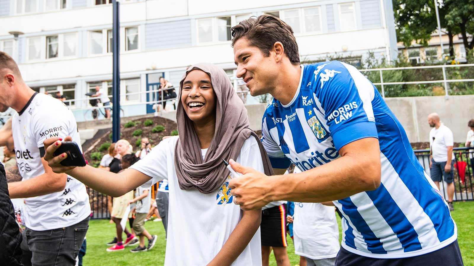 """180808 EN flicka tar en bild med IFK Göteborgs David Boo Wiklander under invigningen av den första fotbollsplanen i """"Planer för Framtiden"""" den 8 augusti 2018 i Göteborg."""